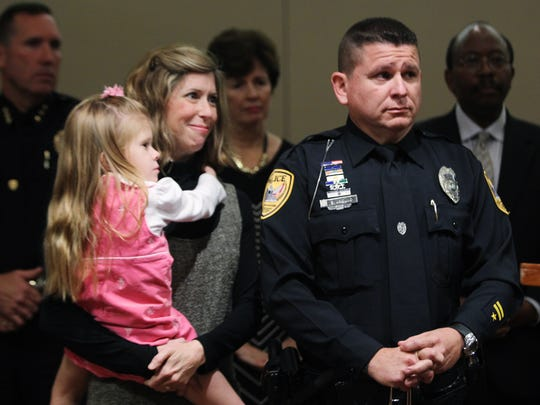 Tallahassee Police Department Officer Scott Angulo stands with his wife, Elizabeth, and daughter, as he is honored by city officials at a commission meeting earlier this month. Angulo was named Officer of the Year by the International Association of Chiefs of Police for his bravery on Nov. 22, 2014, when he took down a gunman on Caracus Court.