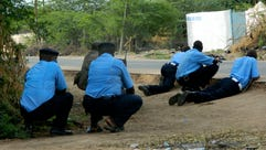 Kenyan police officers take cover outside the Garissa