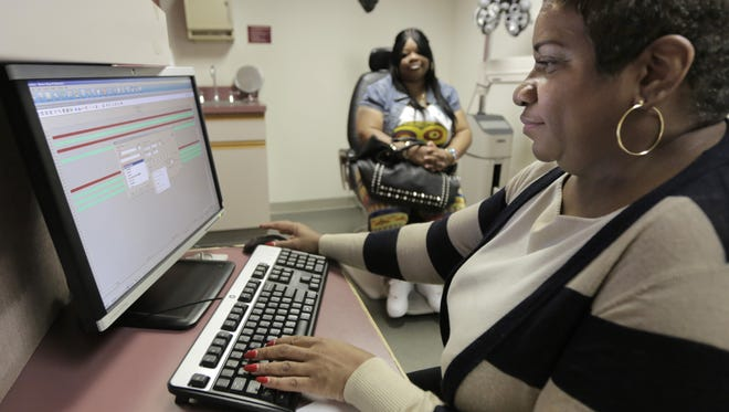 """In this  Sept. 5, 2013,  Jacqueline Saulsberry, a service coordinator at the Illinois Eye Institute, gathers information from patient Shameka Lewis-Coolidge during an appointment in Chicago. With the program known as """"Obamacare"""" only weeks away from its key launch date, hectic preparations are now in motion in communities across the country to deal with one of its major practical challenges: hiring and training a small army of instant experts who can explain the intricacies of health insurance to people whoíve never had it."""