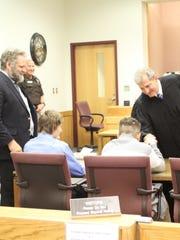 Michigan Supreme Court Justice Brian Zahra hands adoptee