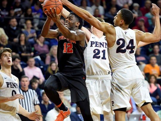 Princeton's Myles Stephens (12) drives past Penn's