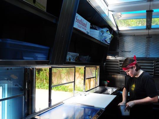 Caroline Perini makes sliders on her food truck, Easy Slider Truck, on June 7, 2012 at a home in Abilene.