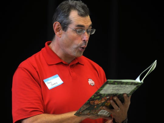 """Volunteer Paul James reads """"The Woodland Elves"""" by local author Shary Williamson and local illustrator Jay Johnston to William H. Taft Elementary School third graders in the school's cafeteria."""