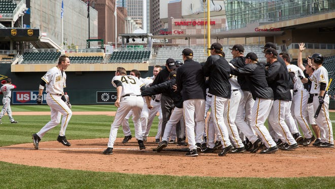 Iowa third baseman Nick Day is greeted at home plate after his walk-off, two-run homer beat Ohio State.