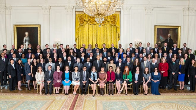 President Barack Obama joins recipients of the Presidential Early Career Award for Scientists and Engineers for a group photo May 5 in the East Room of the White House. Adam Creuziger is in the first standing row, third from the right, between a woman in a red jacket and a woman in a blue dress.
