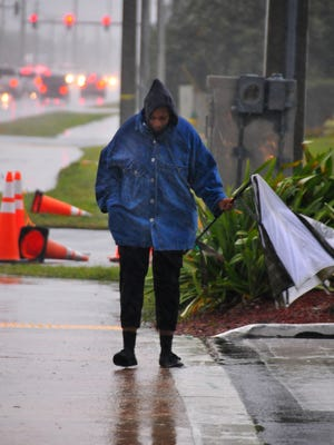 A woman makes her way down A1A during the worst of the storm Wednesday morning, the winds breaking her umbrella. The temperature in Brevard dropped from the '50s to the low '40s in a matter of hours Wednesday morning as high winds and rain hit the Space Coast.