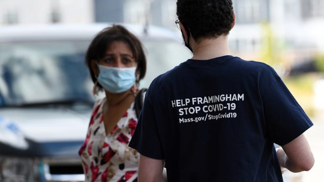Framingham resident Patrick Danahy passes out information and masks during community outreach to increase COVID-19 education at Seabra Foods on Waverly Street in Framingham, Sept. 12, 2020.