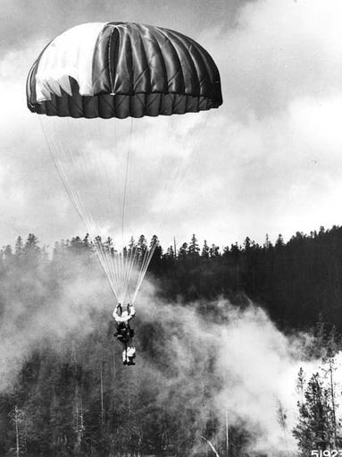 A Forest Service smokejumper descends toward a forest