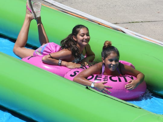 "Participants enjoy the ""Slide the City"" along Main"