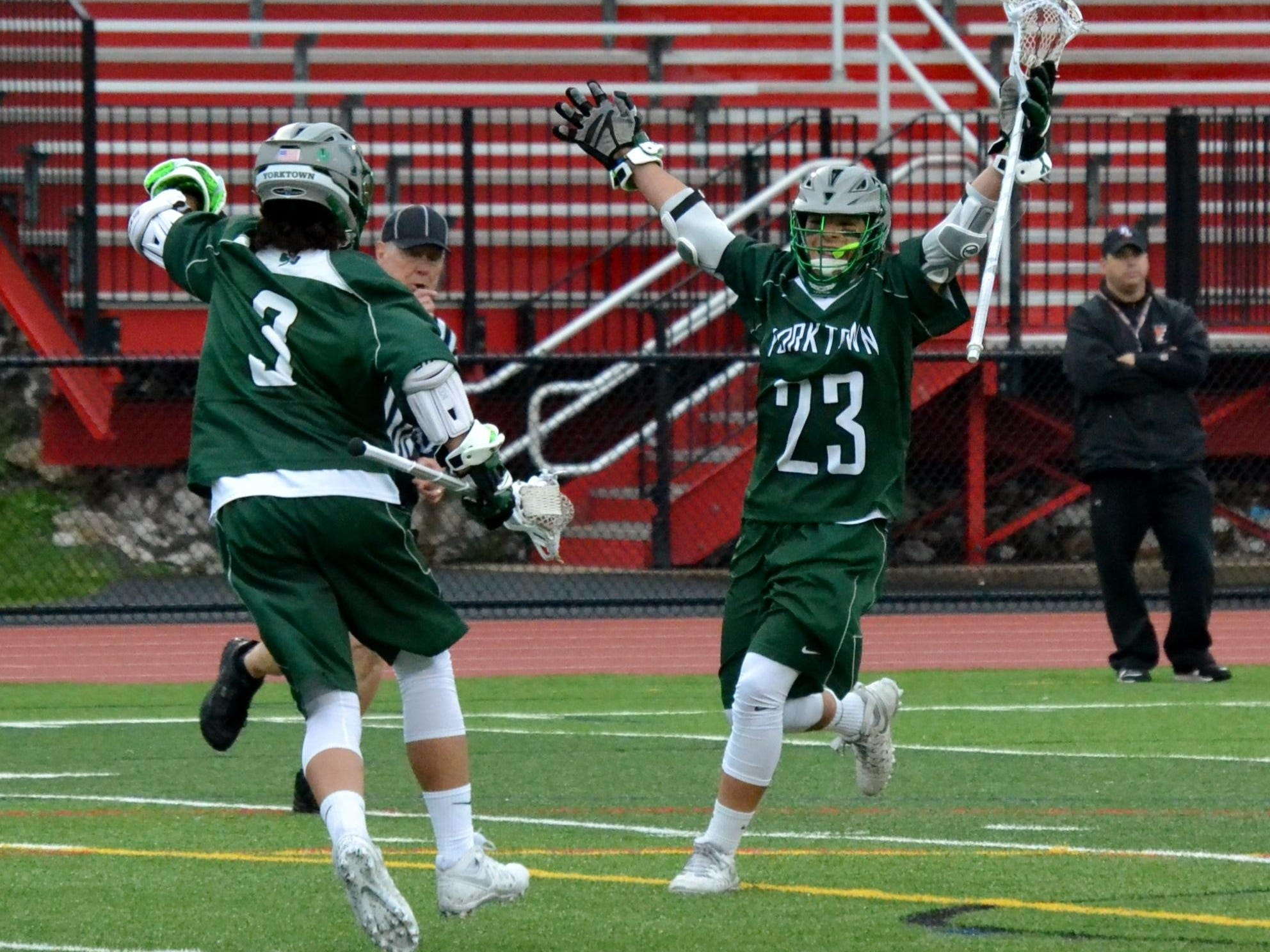 Hunter Embury (23) celebrates a third-period goal with his brother, Jamison. They each scored twice for Yorktown in an 8-6 win at Fox Lane on Tuesday.
