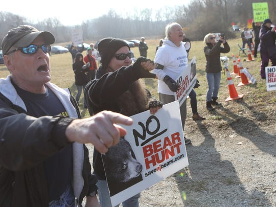 Protesters shout at hunters bringing in dead black bears at the Whittingham Wildlife Management Area in Fredon on Monday.