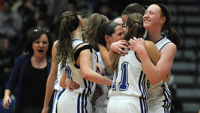 North Harrison's Lilly Hatton (right) is hugged by teammate Shelby Kondovski (11) after defeating Greensburg 46-42 in the Regional Tournament at Charlestown High School. North Harrison head coach Missy Voyles (left) joins in the celebration. Feb.13, 2016