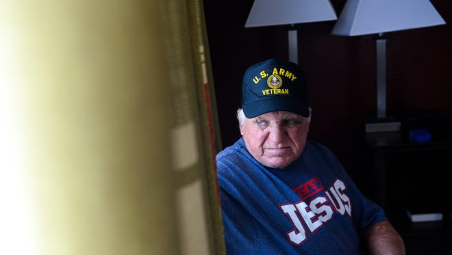 Jessie Alexander, wearing a U.S. Army Veteran cap, recovers from injuries in his room at the Red Roof Inn in Anderson on Tuesday. Alexander said he drove a younger man around in his car around Anderson, before being beaten and robbed Sunday night.