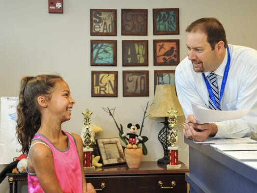 Troy Wood, Bullitt County Schools' new principal at Eastside Middle School, interviews Grace Kelly Lopez, 11, as she transfers from Mt. Washington Middle School because her mother, Anne Lopez, will be teaching S.T.E.M. Science at the school in the fall. July 31, 2014