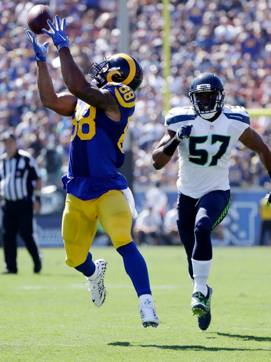 Los Angeles Rams tight end Lance Kendricks, left, makes a catch as Seattle Seahawks outside linebacker Mike Morgan pursues during the first half an NFL football game at Los Angeles Memorial Coliseum, Sunday, Sept. 18, 2016, in Los Angeles. (AP Photo/Jae Hong)