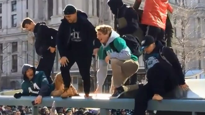 Philadelphia Eagles fans collapse the roof of a bus shelter during the team's Super Bowl parade.
