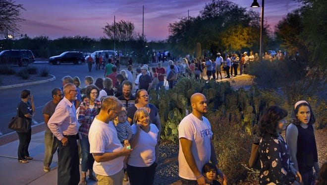 People wait in line to vote at 7 p.m. in the Arizona presidential preference election at the Environmental Education Center in Chandler.