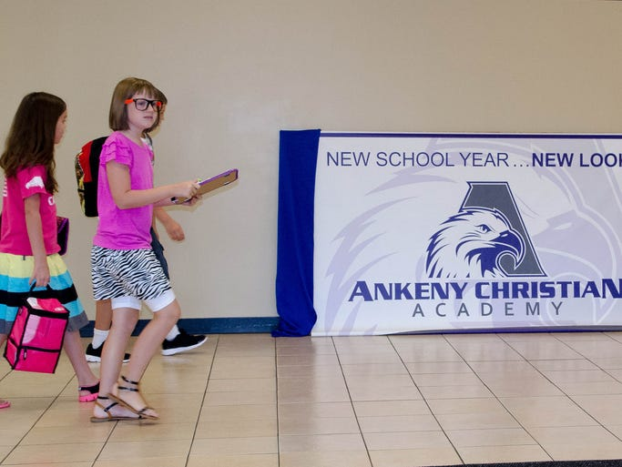 Students on their way to class comment on the banner with the new school logo, which will soon be replaced with a permanent sign.  This took place on the first day back to school at Ankeny Christian Academy on Monday, August 25, 2014.