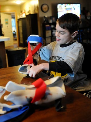 Andrew Nichols demonstrates how to put on his leg braces, decorated with Spider-Man. Andrew hopes that with help from a new drug, Eteplirsen, he and others with Duchenne Muscular Dystrophy may be able to walk again. Andrew will be accompanying his mother, Jodi, as she testifies before the Food and Drug Administration about the effectiveness of the drug.