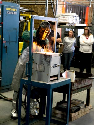 Jared Meibos melts metal to pour into his cast of small gun barrels at Bear Valley Precision Casting on Saturday, March 21, 2015, in Parowan.