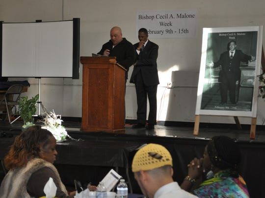 Amos Malone, left, reads a city proclamation that acknowledges the 34th Cecil A. Malone Memorial Week.
