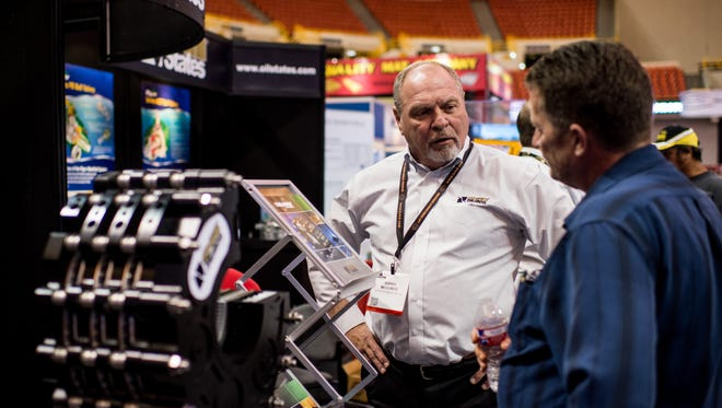 Barry McClintic of Oil States Industries speaks to a booth guest during LAGCOE 2015.