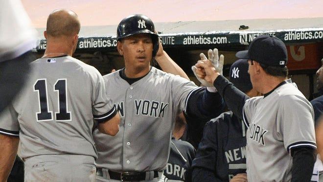 Alex Rodriguez is congratulated by left fielder Brett Gardner, left, and bench coach Rob Thomson.