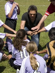 Pistons owner Tom Gores leads the huddle during a youth soccer game.