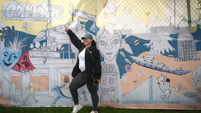"Creative Arts Morgan Village Academy student Makayla Butler stands by her artwork that is part of a 685-foot mural entitled ""Camden, Past. Present. Future."", that was created by Camden students and displayed on the construction fencing at the Camden Waterfront development site, prior to a unveiling ceremony of the mural on Friday morning."