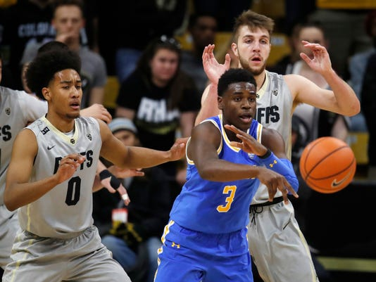UCLA guard Aaron Holiday, front, passes the ball as Colorado guard D'Shawn Schwartz, back left, and forward Lucas Siewert defend in the second half of an NCAA college basketball game Sunday, Feb. 25, 2018, in Boulder, Colo.(AP Photo/David Zalubowski)