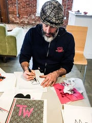 Artist Chris Dacre demonstrates the art of screen printing