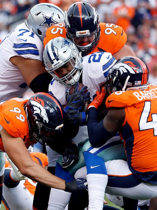 Dallas Cowboys running back Ezekiel Elliott (21) is stopped by Denver Broncos outside linebacker Shaquil Barrett (48), defensive end Derek Wolfe (95) and defensive tackle Adam Gotsis (99) during the first half of an NFL football game, Sunday, Sept. 17, 2017, in Denver. (AP Photo/Jack Dempsey)