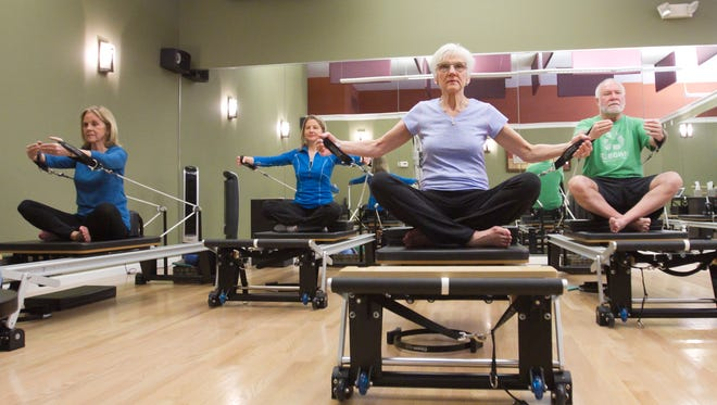 """Performing Pilates in a """"group reformer"""" class at Into Motion in Genoa Township are, from left, Sally Belian, studio director Cherie Boschma, Jane Pendleton and Jeff Sobolewski."""