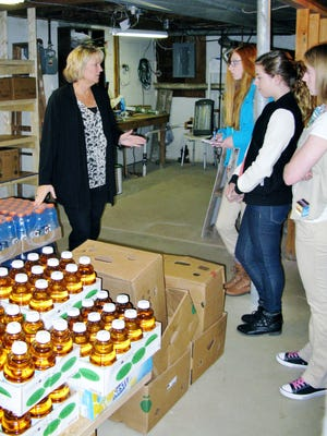 One of the founders of the Penfield Ecumenical Food Shelf, Kathy Cummins, is shown talking to members of visiting Girl Scout Troop 60835.