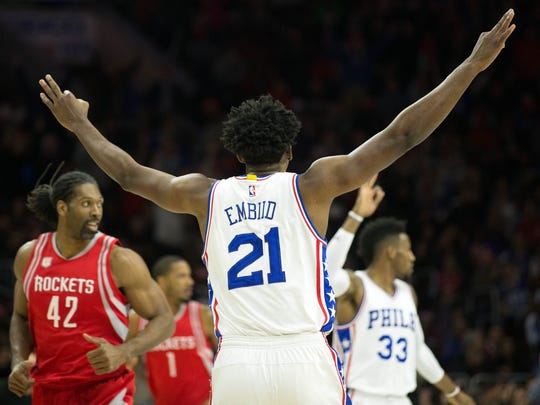 Philadelphia 76ers center Joel Embiid (21) reacts to his three pointer in front of Houston Rockets center Nene Hilario (42) during the first quarter at Wells Fargo Center.