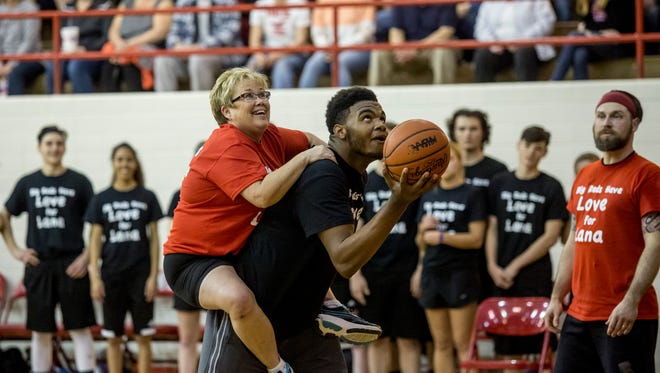 Tricia Ford rides on Tyler Lee's back during the annual Big Reds Believe students vs. staff charity basketball game Friday, March 24, 2017 at Port Huron High School.