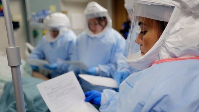 Members of the Department of Defense's Ebola Military Medical Support Team use check lists during training at San Antonio Military Medical Center, Friday, Oct. 24, 2014, in San Antonio. The team will consist of 20 critical care nurses, 5 doctors trained in infectious disease, and 5 trainers in infectious disease protocols. The Michigan Department of Health took one person of its list of people it is monitoring for Ebola.