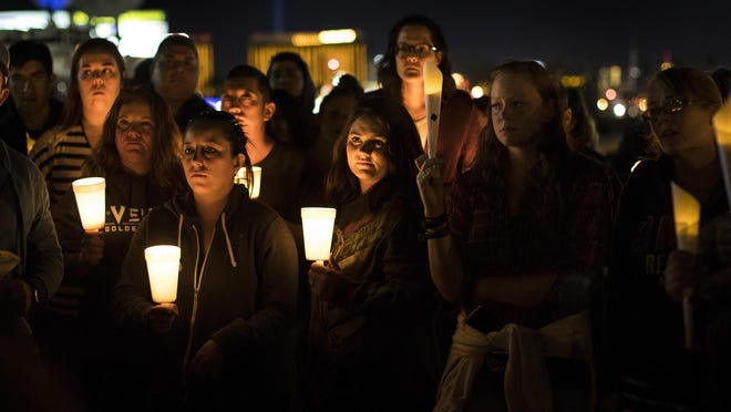 With heavy hearts, people gather for a candlelight vigil at Town Square to remember those killed and injured the day after a lone gunman open fired onto a county music festival from the 32nd floor of Mandalay Bay Hotel, killing 59 and wounding 527 people, on Oct. 2, 2017 in Las Vegas. The Mandalay Bay hotel glows in the background. (Gina Ferazzi/Los Angeles Times/TNS)
