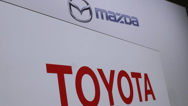 Logos of Toyota Motor Corp., bottom, and Mazda Motor Corp., top, are seen.