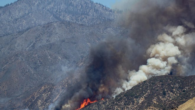 The Apple Fire continues to burn in the foothills north of Cabazon sending up large plumes of smoke on Friday.