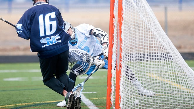 South Burlington's Kyle Murakami scores from close range past Mount Mansfield goalie Will Macone during Saturday's boys lacrosse game in South Burlington.