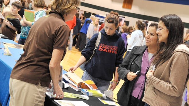 Bee Jai Repp of Portland State University talks with Ramona Garcia and her daughter Grecia Garcia, a junior at West Salem, during the Salem-Keizer College and Career Fair at Chemeketa Community College Monday, Nov. 15, 2010. Organizers said about 900 people attended the fair.