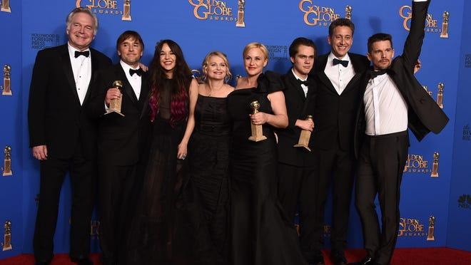 "Jonathan Sehring, from left, Richard Linklater, Lorelei Linklater, Cathleen Sutherland, Patricia Arquette, Ellar Coltrane, John Sloss and Ethan Hawke pose in the press room with the award for best motion picture — drama for ""Boyhood"" at the 72nd annual Golden Globe Awards at the Beverly Hilton Hotel on Sunday in Beverly Hills, California."