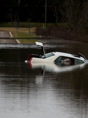 A white car sits in flood water due to heavy rains at the Eastern Flank Park Saturday, Dec. 23, 2017 in Franklin, Tenn.