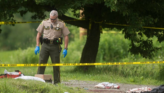 A Vermont state trooper processes a shooting scene on Pettingill Road in Westford Monday.