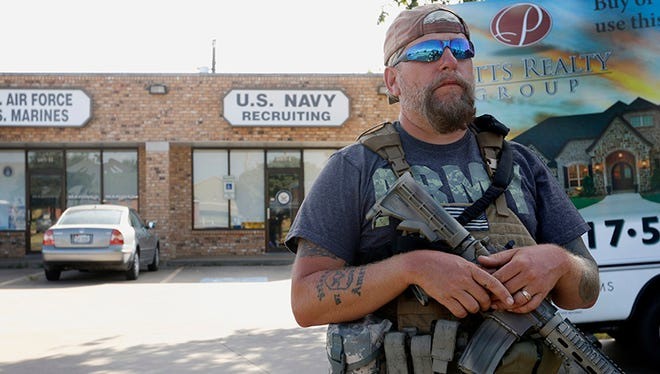 Terry Jackson, a member of Operation Hero Guard, stands guard outside a U.S. military recruiting station in Cleburne, Texas, Tuesday, July 21, 2015. Gun-toting citizens are showing up at military recruiting centers around the country, saying they plan to protect recruiters following last week's killing of four Marines and a sailor in Chattanooga, Tenn.
