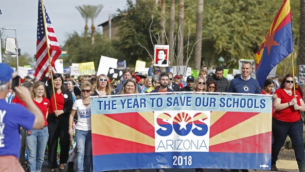 People begin marching during a Save Our Schools rally