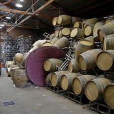 Cellar workers continue cleanup after a number of barrels toppled following an earthquake at the Saintsbury winery Sunday, Aug. 24, 2014, in Napa, Calif. Winemakers in California's storied Napa Valley woke up to thousands of broken bottles, barrels and gallons of ruined wine as a result of Sunday's earthquake.