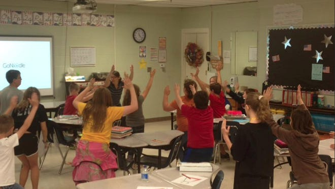 Students at Jennings Randolph Elementary School in Elkins practice yoga in the classroom in fall 2018, led by Tracey Valach, a youth health educator with WVU Extension Service in Randolph County. WVU Extension Photo/Tracey Valach