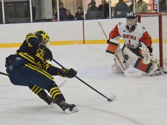 Hartland's Jacob Behnke drives to the net against Brother